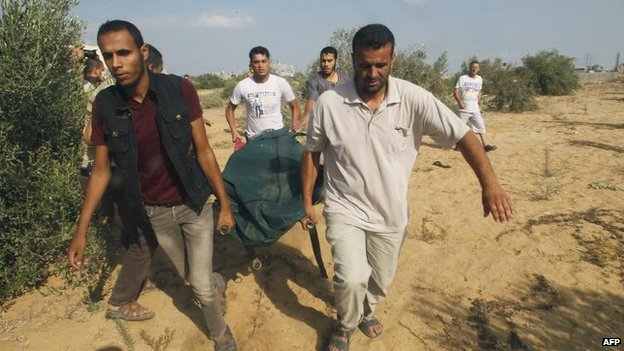 Palestinians remove a body found under rubble in Rafah, southern Gaza, 5 Aug