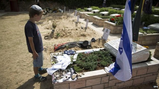 A young Israeli attends the grave of a soldier killed in the Gaza fighting, 5 Aug