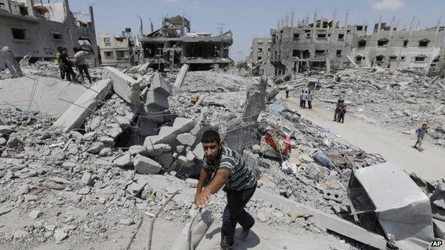 A Palestinian walks on rubble
