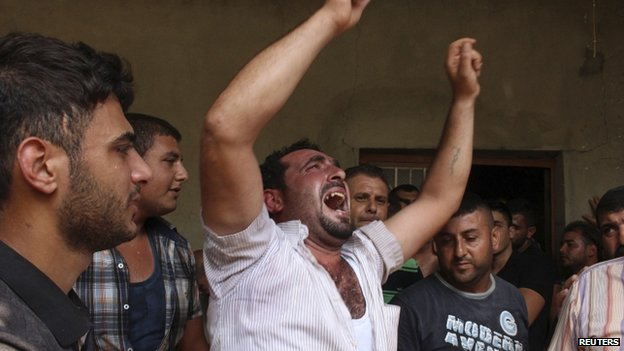 A friend of Alawite soldier Ali Khaddaaro mourns during his funeral in Talhmera village, Akkar, on 5 August 2014.