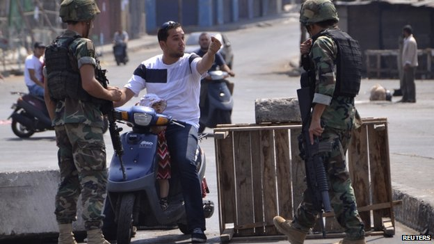 A civilian on a scooter talks to Lebanese army soldiers as he tries to make his way through a blocked road in Lebanon's northern port city of Tripoli on 5 August 2014.