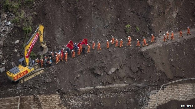 A group of rescue workers walk through a collapsed road at an earthquake hit area in Ludian county, Zhaotong, Yunnan province, 5 August 2014