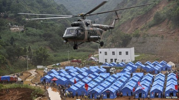 A helicopter prepares to land in front of relief tents at the quake zone in Ludian county, Zhaotong, Yunnan province, on 5 August 2014
