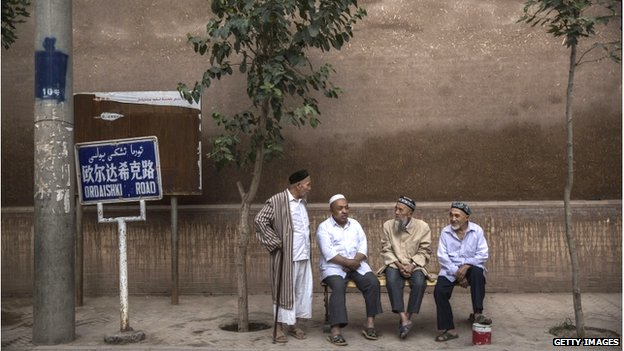 Uighur men chat before evening prayers outside a mosque on 30 July 2014 in old Kashgar, Xinjiang Province, China
