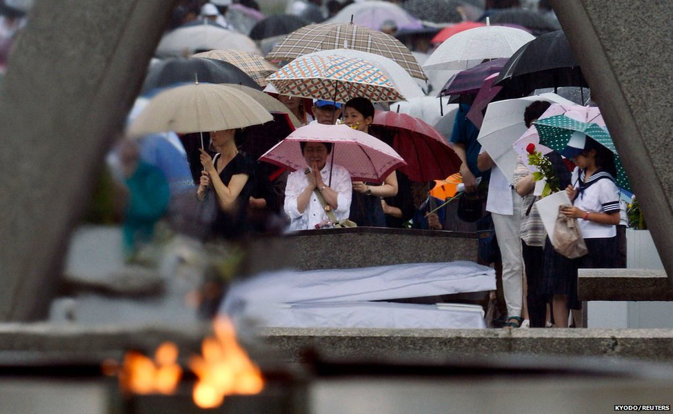People pray at the Peace Memorial Park in Hiroshima, Japan