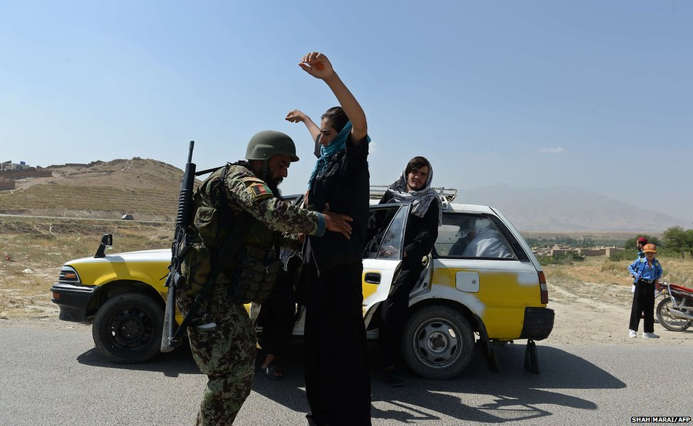 An Afghan National Army (ANA) soldier searches passengers at a checkpoint near the Marshal Fahim National Defense University, a training complex on the outskirts of Kabul