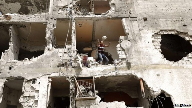 Palestinian man throws an item from a destroyed house in Gaza City on 5 August 2014