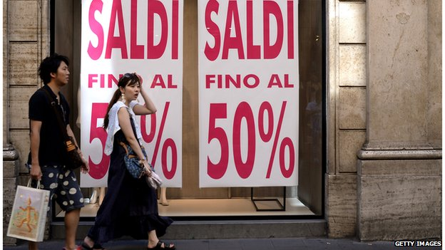 Shoppers outside shop with 50% Sale sign