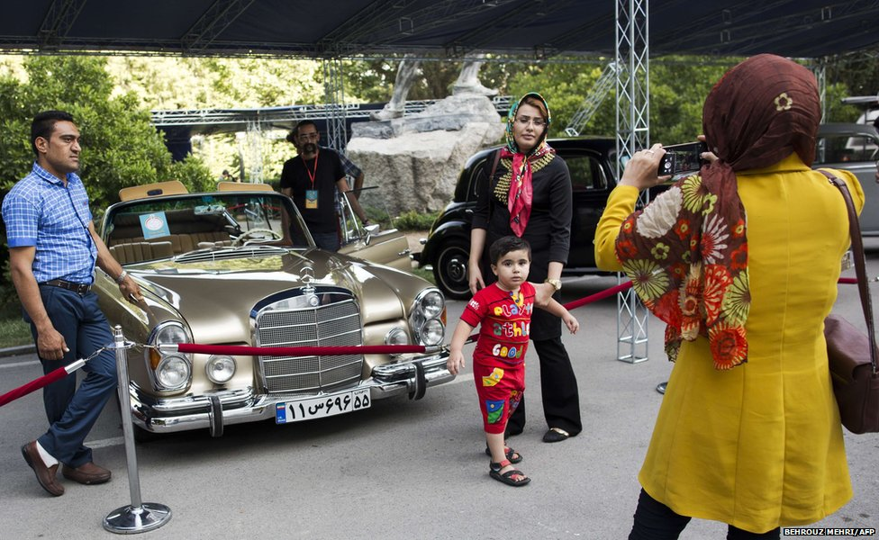An Iranian family poses for pictures a 1961 convertible Mercedes Benz 300 SE