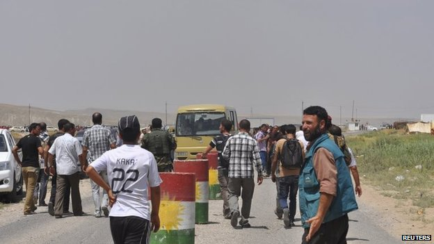 Yazidi families, on the outskirts of Sinjar, flee fighting between Peshmerga and Islamic State fighters (5 August 2014)
