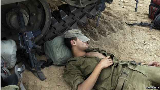 Israeli soldier resting beside tank in southern Israel on 6 August 2014