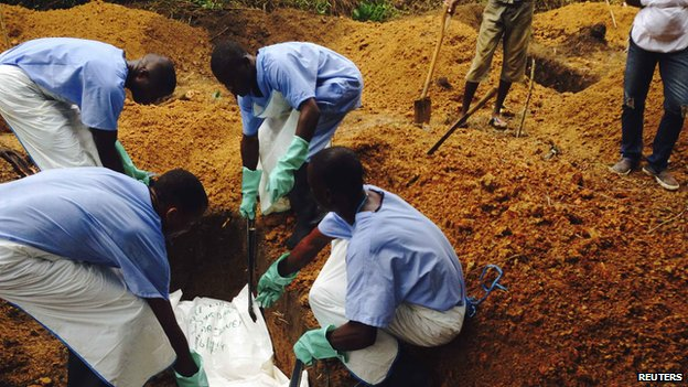 Volunteers bury the body of an Ebola victim in Sierra Leone