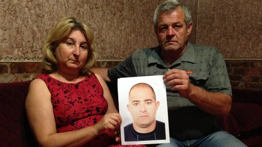 Seitumer Zinedinov and his wife Elvira hold a picture of their missing son Seiran