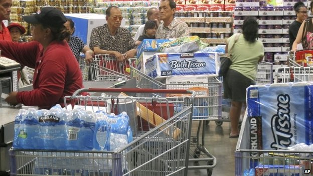 Shoppers stock up on cases of bottled water and other supplies in preparation for a hurricane and tropical storm heading toward Hawaii at the Iwilei Costco in Honolulu on 5 August 2014