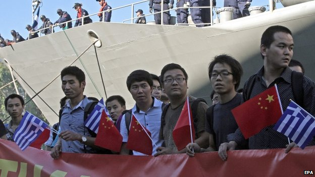 Evacuees from China hold a banner after they disembarked from a Greek Navy warship in Piraeus, Greece (2 August 2014)