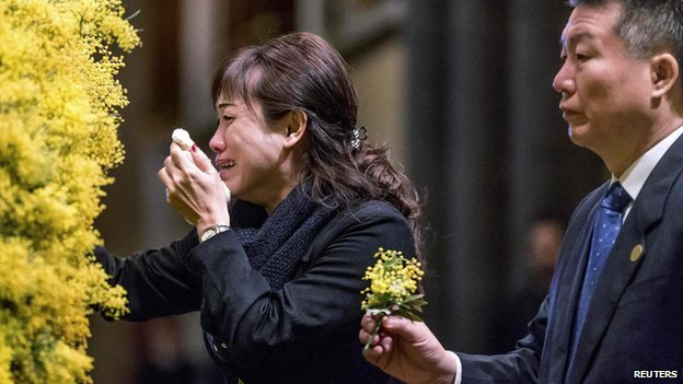 Mourners place sprigs of wattle blossoms on a wreath during a national memorial service for the victims of Malaysia Airlines flight MH17 at St Patrick's Cathedral in Melbourne on 7 August, 2014