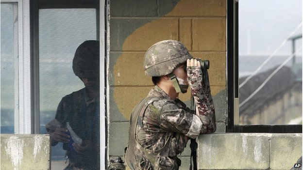 A South Korean army soldier looks through a pair of binoculars at a military check point at the Imjingak Pavilion near the border with North Korea, South Korea, Sunday, 13 July 2014.