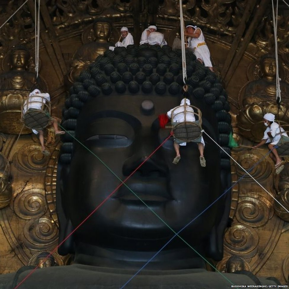 Buddhist monks clean dust off of the 15m (50ft) high Great Buddha at the Todaiji Temple in Nara, Japan