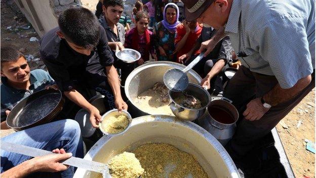 Iraqi Yazidi families receive food handouts in Dohuk in Iraq's autonomous Kurdish region (photo taken on 5 August 2014)