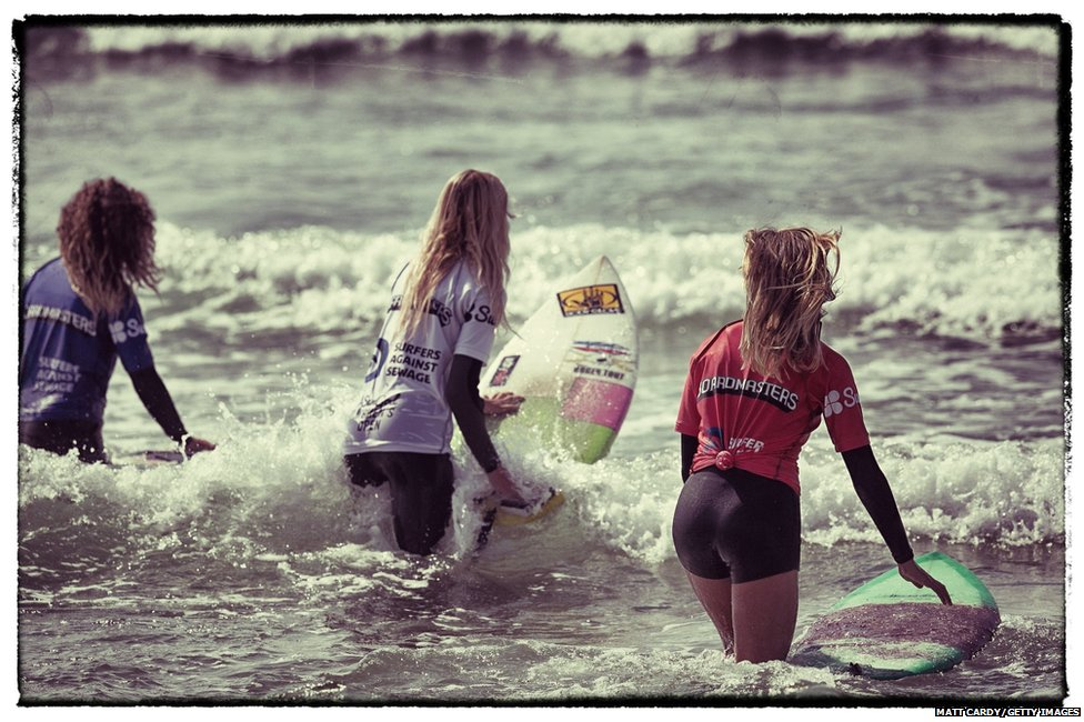 Corine Evans, Beth Wallace and Jess Knight paddle out into the sea before competing in a heat of the Sun God Women's Event at Fistral Beach on the first day of the Boardmasters surf and music festival in Newquay c