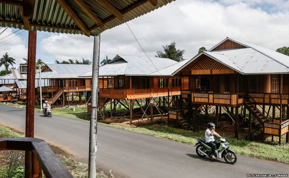 Motorcyclists pass a row of prefabricated wooden houses in Woloan Village, Tomohon, North Sulawesi, Indonesia