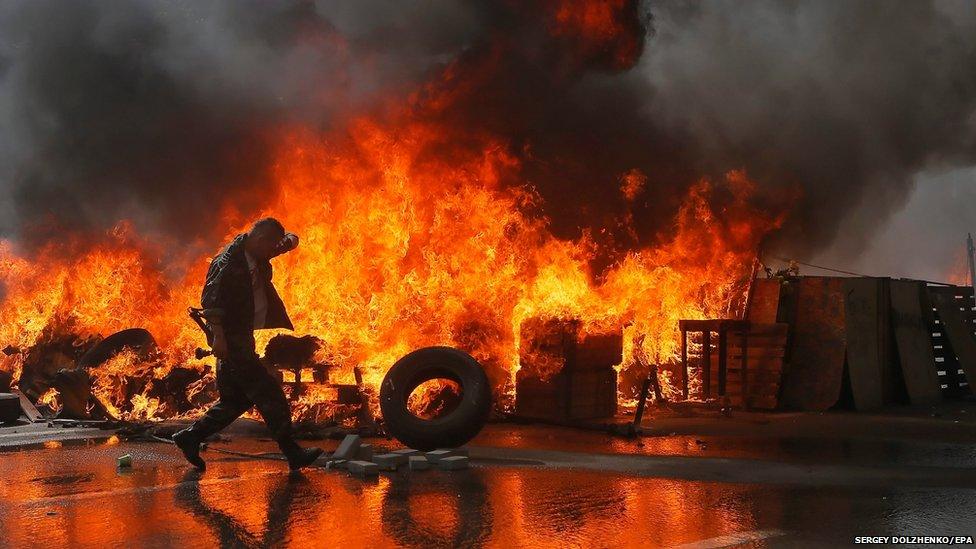 A Maidan activist burns tires