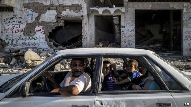 Palestinian family drive past damaged buildings in Gaza City (6 August 2014)
