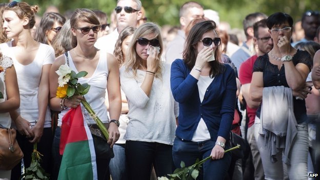 People cry as they take part in a silent march on 3 August 2014 in Rouans, western France, in memory of the seven members of the Ouedraogo family who were aboard the Air Algerie plane that crashed over Mali
