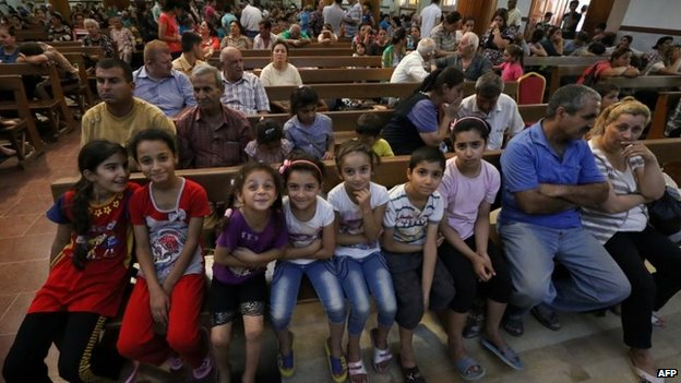 Iraqi Christians who fled the violence in the village of Qaraqush, about 30 kilometres east of the northern province of Nineveh, sit in Saint-Joseph church in the Kurdish city of Erbil