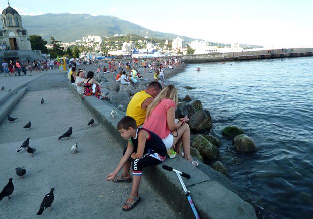 Boy feeding pigeons in Yalta
