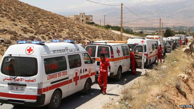 A convoy of Red Cross vehicles evacuate casualties from the Sunni Muslim border town of Arsal, in eastern Bekaa Valley