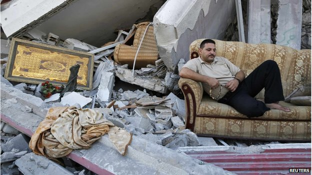 A man sitting on a sofa on top of a pile of rubble