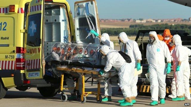 Medics load Miguel Pajares' protective chamber onto an ambulance