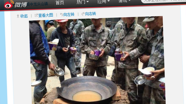 Soldiers eating noodles around a bowl of dirty water