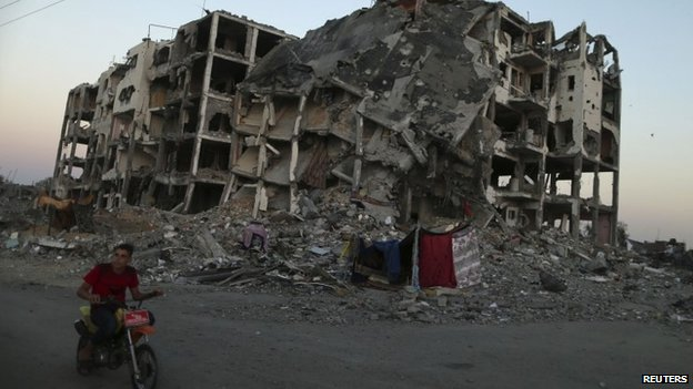 A Palestinian rides past residential buildings in Beit Lahiya town, which witnesses said was heavily hit by Israeli shelling and air strikes during the offensive in the northern Gaza Strip (7 August 2014)