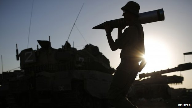 An Israeli soldier carries a tank shell in a staging area near the border with the Gaza Strip (7 August 2014)