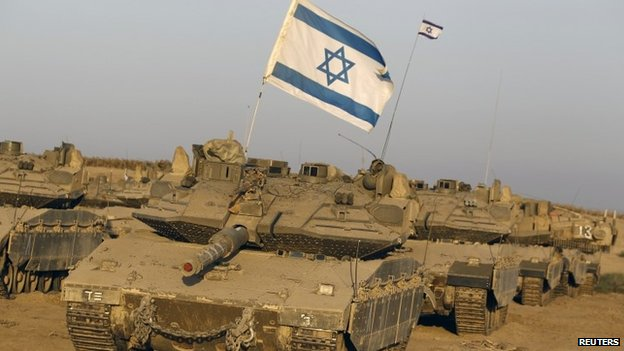 Israeli tanks are seen in a staging area near the border with the Gaza Strip (7 August 2014)