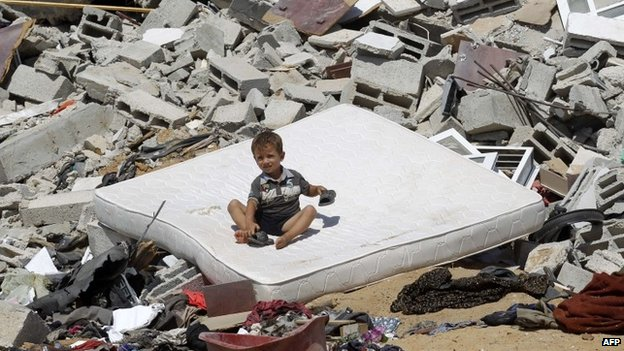 A Palestinian child sits on a mattress on the rubble of a house which was destroyed in an Israeli air strike on Abasan, east of the southern Gaza Strip town of Khan Yunis and close to the border with Israel (7 August 2014)