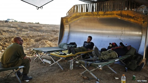 Israeli soldiers rest at a staging area near the border with the Gaza Strip (7 August 2014)