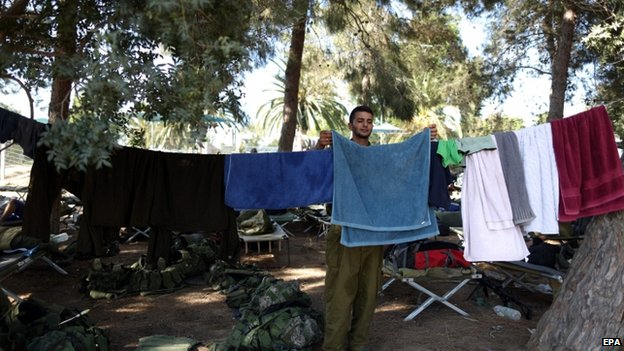An Israeli reserve soldier hangs his laundry at an unspecified location near the Israeli border with the Gaza Strip (7 August 2014)