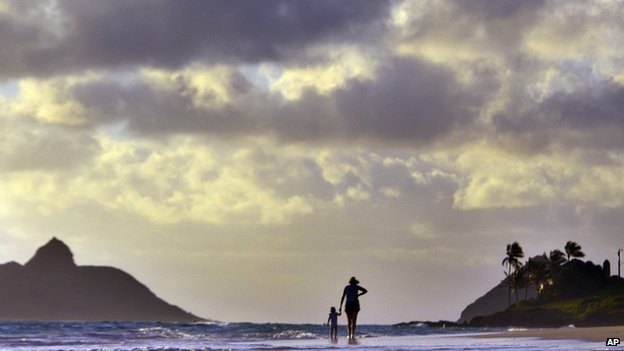 Anne Kllingshirn of Kailua, Hawaii walks with her daughter Emma, 1, as storm clouds are are seen during the sunrise hours on Kailua Beach, in Kailua, Hawaii, 7 August 2014