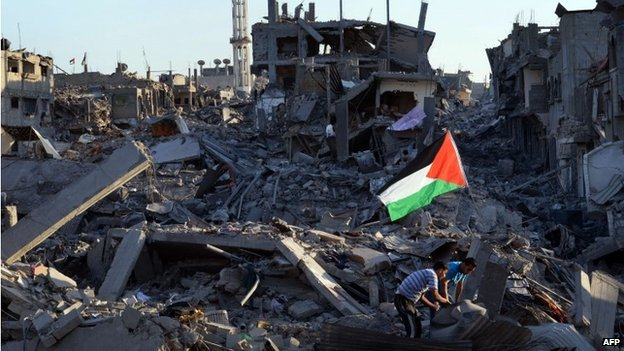 Residents walk through the rubble in the devastated neighbourhood of Shejaiya in Gaza City (7 August 2014)