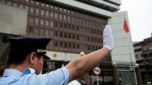 A policeman gestures in front of the Shanghai Intermediate Court on 8 August 2014