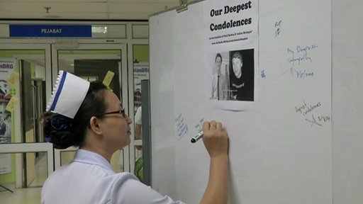 Staff at Sarawak General Hospital sign a condolence board