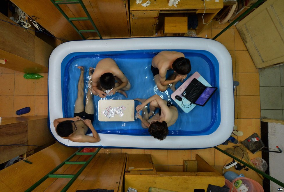 College students cool off inside an inflatable pool at their dormitory