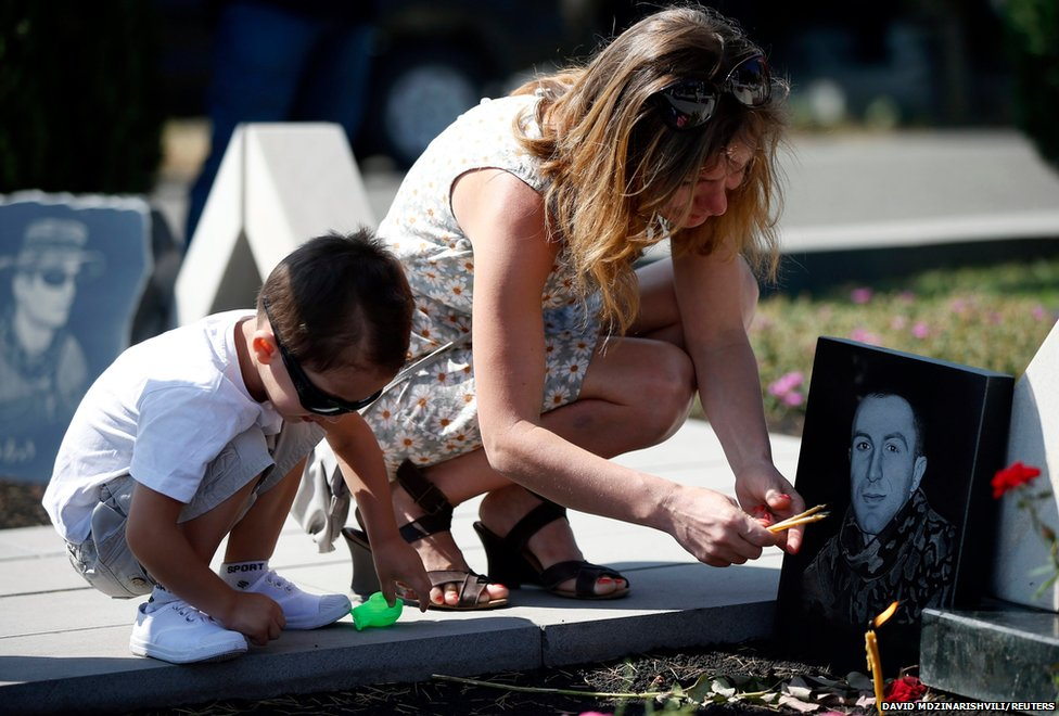 Relatives of a Georgian soldier  light candles during a ceremony at the memorial cemetery in Tbilisi.
