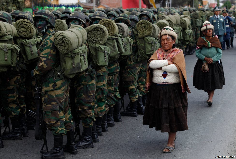 Aymara women walk past a battalion before the start of a military parade during Independence Day celebrations, in La Paz, Bolivia