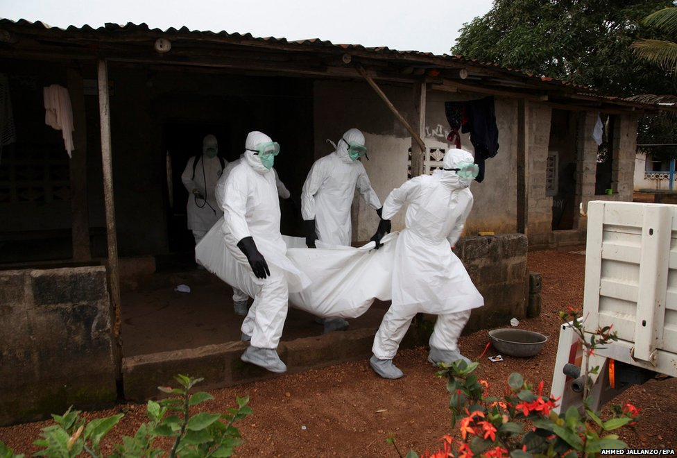 Liberian nurses carry the body of an Ebola victim from a house for burial in the Banjor Community on the outskirts of Monrovia, Liberia