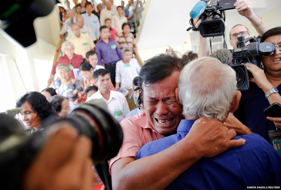 Soum Rithy (centre), who lost his father and three siblings during the Khmer Rouge regime, breaks out in tears and hugs another survivor