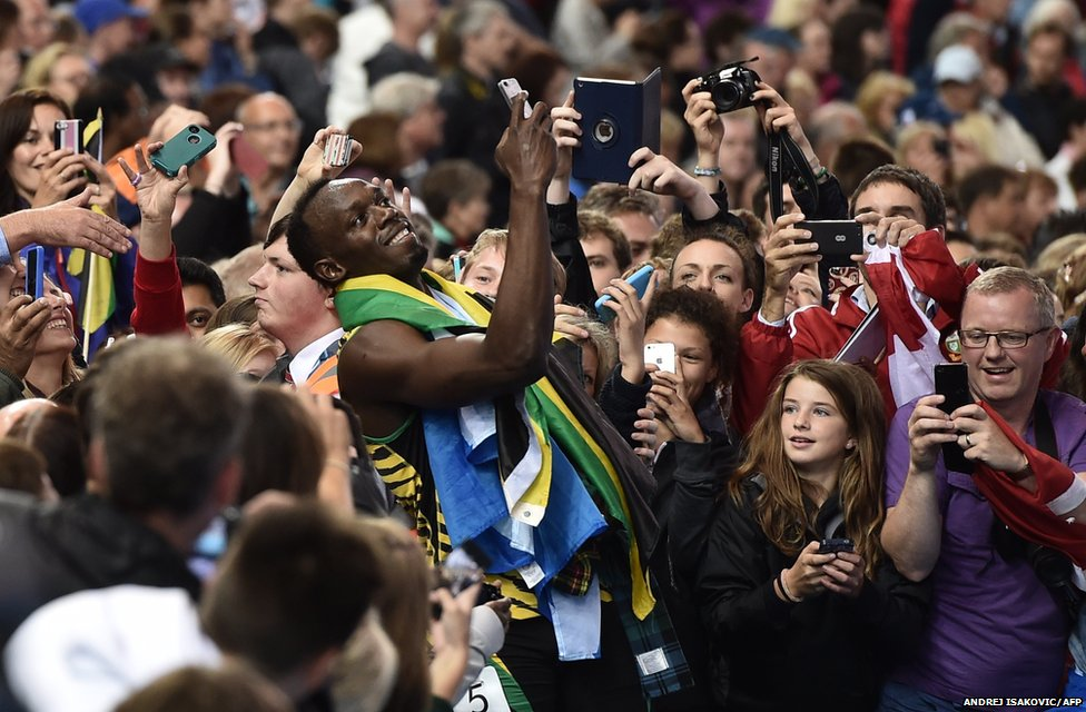 Jamaica's Usain Bolt poses for fans at the Commonwealth Games in Glasgow